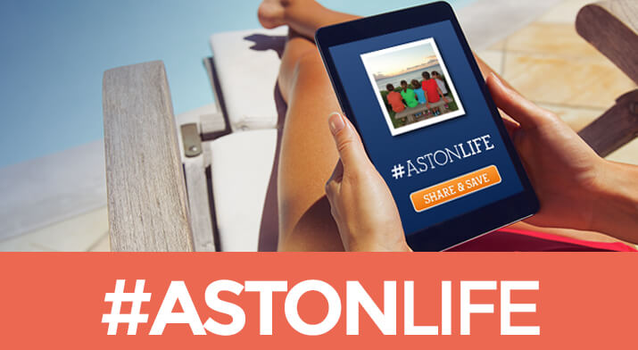 Woman sitting on a lounge chair with tablet showing #AstonLife promo
